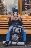 Muchacha que se sienta en un banch y que usa un teléfono Imagen de archivo libre de regalías