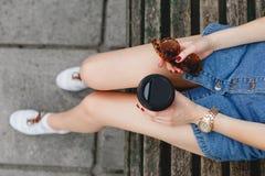 Muchacha que se sienta en un banco de madera con la taza de café Imagenes de archivo