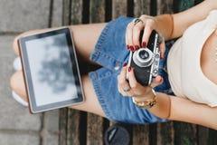 Muchacha que se sienta en un banco de madera con la taza de café Fotos de archivo libres de regalías