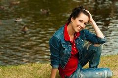 muchacha que se sienta en un banco en un jardín verde del verano Fotografía de archivo libre de regalías