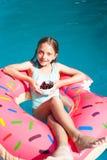 Muchacha que se sienta en un buñuelo inflable colorido con las cerezas Imagenes de archivo