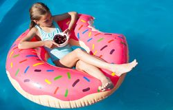 Muchacha que se sienta en un buñuelo inflable colorido con las cerezas Foto de archivo