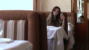 Muchacha que se sienta en un café con un vidrio de champán almacen de video
