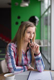 Muchacha que se sienta en un café y un pensamiento fotografía de archivo