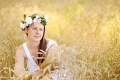 Muchacha que se sienta en un campo de trigo maduro Imagen de archivo