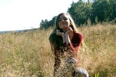 Muchacha que se sienta en un campo en la hierba de oro fotografía de archivo