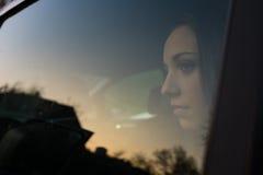 Muchacha que se sienta en un coche Foto de archivo libre de regalías