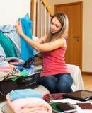 Muchacha que se sienta en un cuarto cerca de la maleta Imágenes de archivo libres de regalías