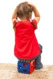 muchacha que se sienta en un juguete plástico rojo con las manos para arriba Fotografía de archivo libre de regalías