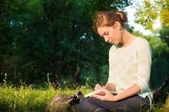 muchacha que se sienta en un parque y que escribe en un cuaderno Imágenes de archivo libres de regalías