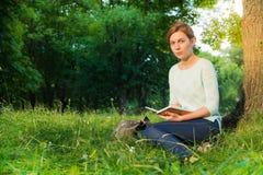 muchacha que se sienta en un parque y que escribe en un cuaderno Fotos de archivo libres de regalías