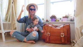 Muchacha que se sienta en un piso con un bebé y una maleta almacen de video