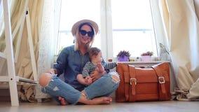 Muchacha que se sienta en un piso con un bebé y una maleta almacen de metraje de vídeo