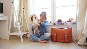 Muchacha que se sienta en un piso con un perro y una maleta almacen de video