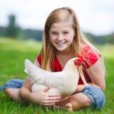 Muchacha que se sienta en un prado con su pollo Foto de archivo libre de regalías