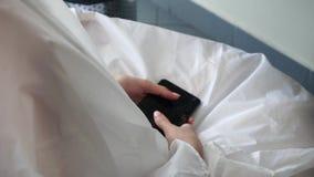 Muchacha que se sienta en un salón de belleza, sosteniendo un teléfono en sus manos almacen de metraje de vídeo
