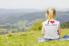 muchacha que se sienta en un top de la montaña Fotos de archivo