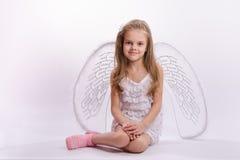 Muchacha que se sienta en un traje del ángel en un fondo blanco Fotos de archivo libres de regalías