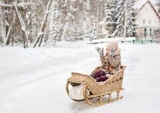 Muchacha que se sienta en un trineo de madera del vintage y que cubre feliz sus manos de la nieve Foto de archivo libre de regalías