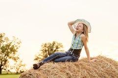 Muchacha que se sienta en una bala de heno en el país Imágenes de archivo libres de regalías