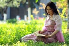 Muchacha que se sienta en una hierba Imagen de archivo