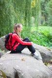 Muchacha que se sienta en una piedra grande, naturaleza del otoño Fotos de archivo libres de regalías