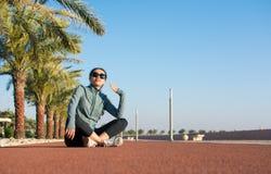 Muchacha que se sienta en una pista corriente y que disfruta de día soleado Imagenes de archivo