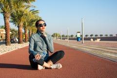 Muchacha que se sienta en una pista corriente y que disfruta de día soleado Fotografía de archivo libre de regalías
