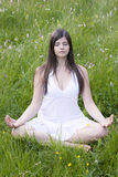 Muchacha que se sienta en una posición de la yoga en prado Foto de archivo