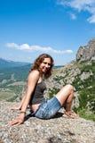 Muchacha que se sienta en una roca imágenes de archivo libres de regalías
