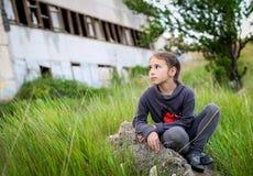 Muchacha que se sienta en una roca Foto de archivo libre de regalías
