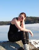 Muchacha que se sienta en una roca en invierno Foto de archivo libre de regalías