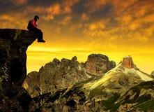 Muchacha que se sienta en una roca en la puesta del sol Fotos de archivo libres de regalías