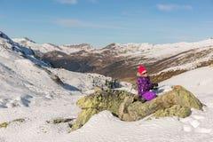 Muchacha que se sienta en una roca en las montañas nevosas Fotos de archivo libres de regalías