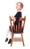Muchacha que se sienta en una silla Imagen de archivo