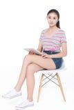 Muchacha que se sienta en una silla Fotografía de archivo