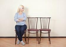 Muchacha que se sienta en una silla Fotos de archivo
