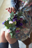 Muchacha que se sienta en una silla y que sostiene un ramo de flores en ella Fotografía de archivo libre de regalías