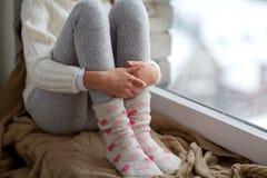 Muchacha que se sienta en ventana del travesaño en casa en invierno Imagenes de archivo