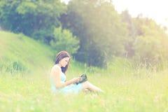 Muchacha que se sienta leyendo un libro al aire libre Imágenes de archivo libres de regalías