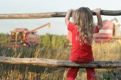 Muchacha que se sienta observando el campo de granja con la máquina segadora de trabajo roja fotografía de archivo