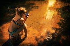 Muchacha que se sienta por el agua con una taza Fotografía de archivo