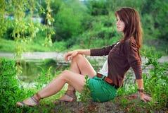 Muchacha que se sienta por el lago Fotografía de archivo libre de regalías