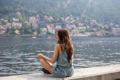 Muchacha que se sienta por el lago Imágenes de archivo libres de regalías
