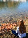 Muchacha que se sienta por el lago Imagen de archivo libre de regalías