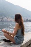 Muchacha que se sienta por el lago, meditando Fotografía de archivo libre de regalías