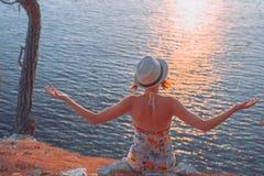 Muchacha que se sienta por el mar en la puesta del sol y que se relaja foto de archivo