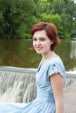 muchacha que se sienta por el río Foto de archivo libre de regalías