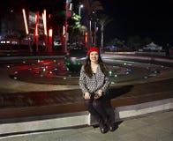 Muchacha que se sienta por la fuente en la noche imagen de archivo libre de regalías