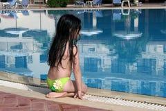 Muchacha que se sienta por la piscina Fotografía de archivo libre de regalías